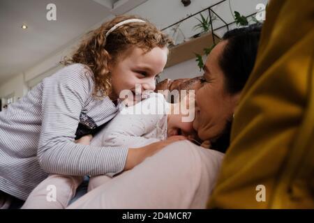 Mère et deux filles jouant ensemble et riant en mentant les uns avec les autres sur un canapé confortable dans la salle de séjour