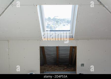 Extension de loft dans la maison, murs et plafonds en plâtre, fenêtre sur le toit Banque D'Images