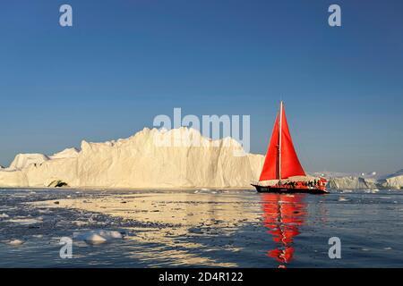 Bateau à voile rouge devant les icebergs, Icefjord, patrimoine mondial de l'UNESCO, baie de Disko, Ilulissat, ouest du Groenland, Groenland, Amérique du Nord