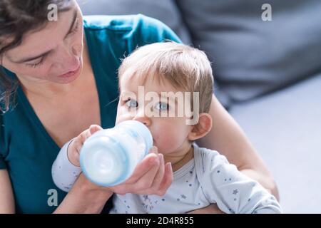 bébé fille de 9 mois qui boit du lait dans un biberon.