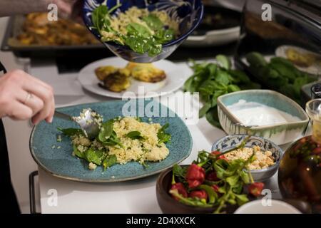 Gros plan des mains de la femme portant une salade végétarienne fraîche avec du cous. Femme cuisant dans la cuisine à la maison préparant des aliments sains. Méditerranée