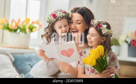 Bonne fête des mères ! Enfants félicitant maman. Maman et fille souriant et enserrer. Vacances en famille et ensemble.