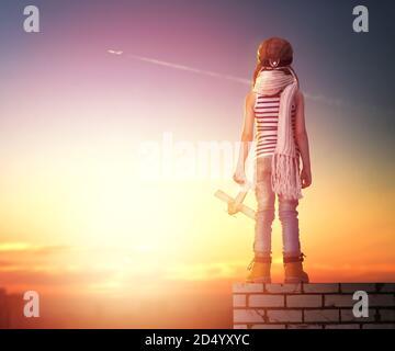 un enfant joue avec un avion jouet au coucher du soleil et rêve de devenir pilote