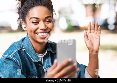 Femme africaine avec smartphone faisant appel vidéo assis à Park Banque D'Images