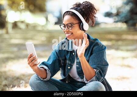 Une dame africaine s'est mise à l'extérieur sur un smartphone Banque D'Images