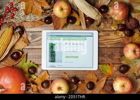 Bonjour septembre. Automne plat avec tablette pc avec nourriture biologique magasin en ligne, maïs, citrouille, pommes, rowan, châtaignes et feuilles sur des planches en bois.