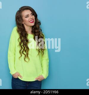 Décontracté jeune femme en vert citron vert est tenant les mains dans les poches et regardant loin. Taille haute studio tourné sur fond bleu.