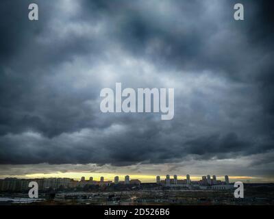 Une tempête suronde la ville. Ciel noir dans les nuages et la ligne du coucher de soleil orange. Zone industrielle sur fond de bourdes imminentes