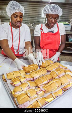 Florida Miami Easter Seals Intergénérationnel Day, cuisine bénévoles préparer la nourriture jeunes Africains noirs, travail des cheveux, Américains Banque D'Images