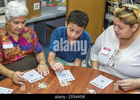 Florida Miami Easter Seals Intergénérationnel Day, senior senior femme femme hispanique adolescent garçon volontaire jouant au bingo américain Banque D'Images