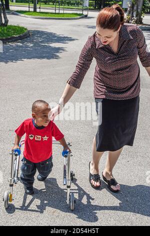 Floride Miami-Dade Easter Seals Intergénérationnel Day personnel client Black African Hispanique femme handicapée handicapés besoins spéciaux garçon marcheur américain Banque D'Images