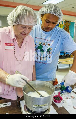 Florida Miami Easter Seals les bénévoles de la Journée intergénérationnelle préparent le déjeuner Repas hispaniques noires africaines femmes travaillant américaines Banque D'Images