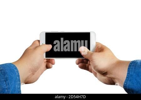 Première personne isolée visualiser la photo d'un homme mains dans un Jean chemise tenant et jouant un smartphone horizontalement sur fond blanc.