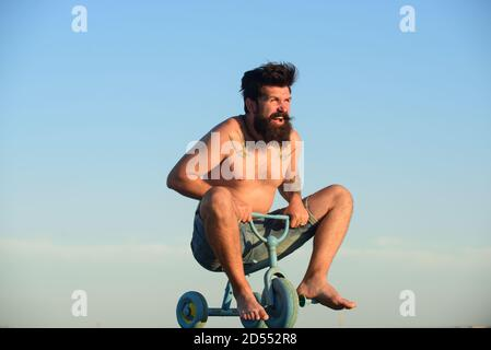 Guy tricycle d'équitation pour enfants. Jeune homme fou à vélo à trois roues.