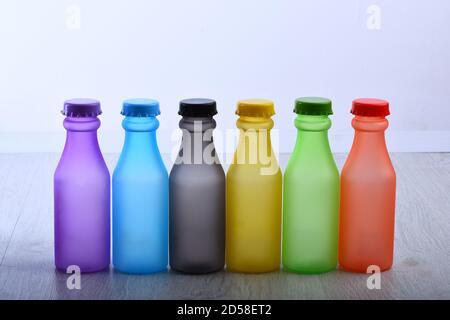 Peinture colorée. Flacons avec pigments secs colorés sur fond de bois blanc. Couleurs arc-en-ciel : choisir la bonne couleur. Concept de boissons colorées Banque D'Images