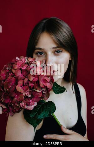 Portrait d'une jeune femme tenant une hortensia