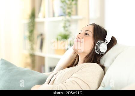 Une femme satisfaite se détendant sur un canapé pour écouter de la musique à la maison