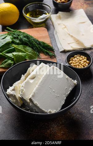 Fromage feta traditionnel dans un bol noir vue latérale devant les ingrédients.