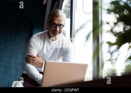 Décontracté gris-cheveux homme mature dans des lunettes de vue travaillant sur ordinateur portable pendant assis dans un bureau ou un café près de la fenêtre