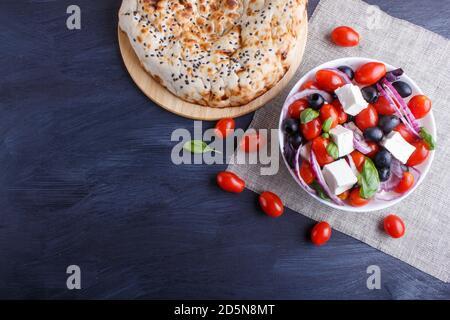 Salade grecque avec tomates cerises fraîches, fromage feta, olives noires, basilic et oignon sur fond de bois noir, crêpes, vue de dessus, espace copie.
