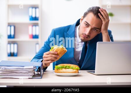 Jeune employé prenant le petit déjeuner sur le lieu de travail Banque D'Images