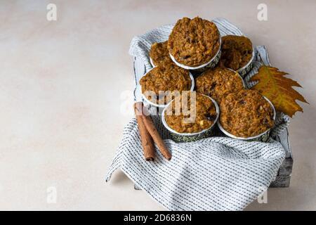 Des muffins à la carotte ou à la citrouille maison végétaliens sains avec raisins secs et noix, fond clair.