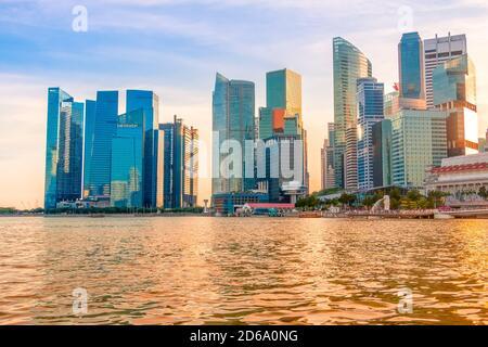 Soirée Singapour. Gratte-ciel sur la rive de Marina Bay. Le soleil teinte l'eau d'or. Banque D'Images