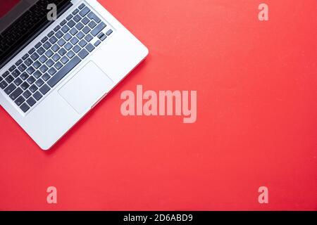 Ordinateur portable sur fond rouge vif. Vue du dessus de l'ordinateur portable ouvert, couleur argent et métal. Concept de bureau à domicile, espace de copie, modèle Banque D'Images