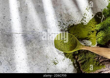Chlorella en poudre verte, spiruline sur fond de béton gris. Concept de régime, de détox, de superalimentation saine, qui contient des protéines.