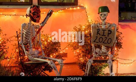 Deux squelettes assis sur des chaises à l'extérieur d'une maison pour Halloween