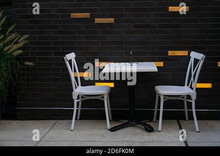 Une table et des chaises blanches pour deux personnes en vertu des règles de distanciation sociale pendant la pandémie de covid-19 à un café-terrasse