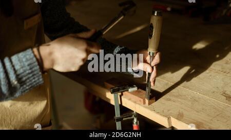 Gros plan des mains de charpentier travaillant avec un marteau dans un petit atelier de menuiserie. Jeune femme travailleuse de bois travaillant sur un morceau de bois pour une nouvelle maison d