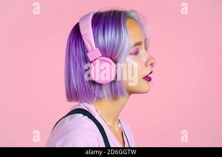 Gros plan portrait d'une jolie fille aux cheveux violets teints écoutant de la musique, souriant, dansant dans un casque en studio sur fond rose. Musique Banque D'Images