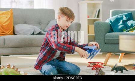 À la maison : Smart Little Boy joue avec Toy Airplane. Un jeune enfant joue sur un tapis dans la salle de séjour Sunny.