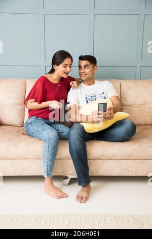 Jeune couple asiatique indien utilisant un smartphone ensemble tout en étant assis canapé ou canapé et espace intérieur ou maison moderne