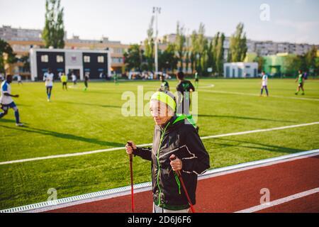 Reste actif du thème des personnes âgées. Sports et santé à la retraite. Caucasien très vieille femme avec des rides profondes faisant des exercices de marche nordique avec