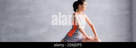 Prise de vue panoramique de la sportswoman en fente sur fond gris Banque D'Images