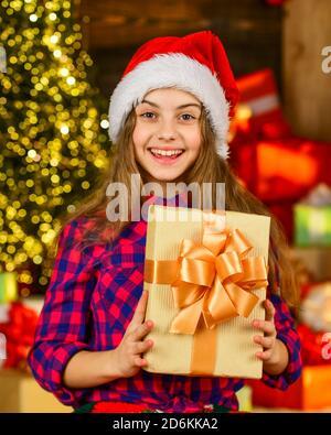 Surprise inattendue. Portrait enfant avec cadeau. Temps libre et joie. Enfant en chapeau de père noël. Matin avant Noël. Jolie petite fille avec des cadeaux. Les enfants aiment les vacances. Les vacances d'hiver et les vacances. Banque D'Images