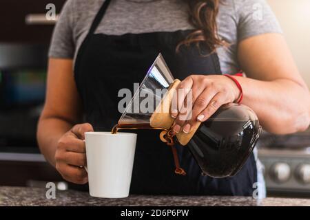 Une femme hispanique Barista verse du café dans une tasse blanche dans la cuisine familiale. Femme noire tenant verser sur la cafetière le matin
