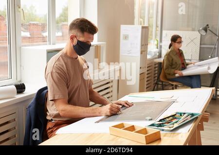 Vue latérale d'un architecte barbu mature portant un masque tout en étant assis au bureau à la lumière du soleil, dans un espace de copie