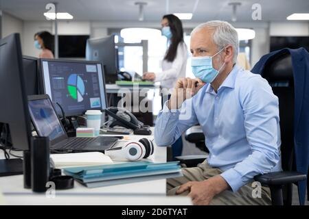 Homme d'affaires senior attentif portant un masque de visage assis sur son bureau au bureau moderne