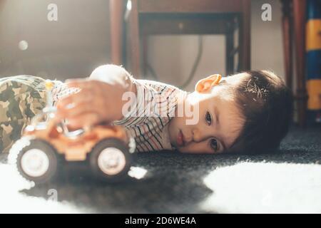 Garçon caucasien couché sur le sol et jouant avec un voiture-jouet pendant une journée ensoleillée