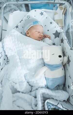 Adorable bébé nouveau-né dormant paisiblement dans son berceau dans la chambre d'hôpital avec un jouet doux. Photo de haute qualité Banque D'Images
