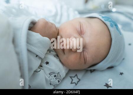 Adorable bébé nouveau-né dormant paisiblement dans son berceau dans la chambre d'hôpital. Photo de haute qualité Banque D'Images