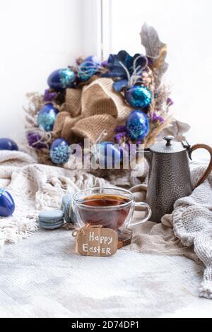 Ambiance chaleureuse pour Pâques, printemps encore. Petit déjeuner avec thé et dessert macarons. Le concept des vacances de Pâques et la décoration.