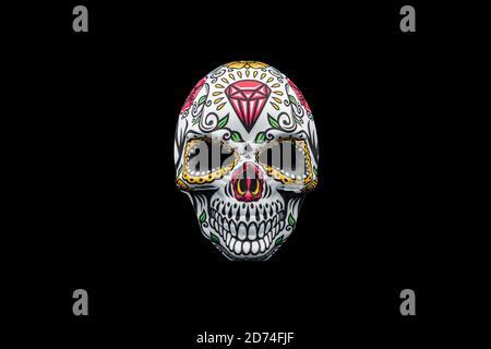 Masque d'Halloween représentant un crâne mexicain traditionnel avec un motif floral coloré isolé sur un fond noir.