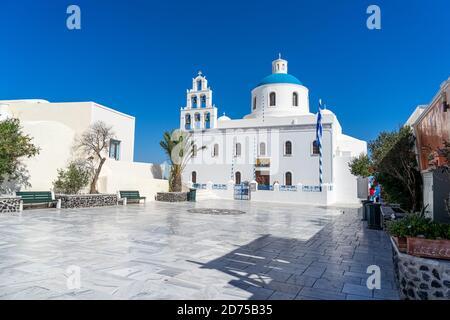 Eglise orthodoxe à Oia, Santorin, Grèce, un jour d'été avec drapeau grec. Beau ciel bleu clair.