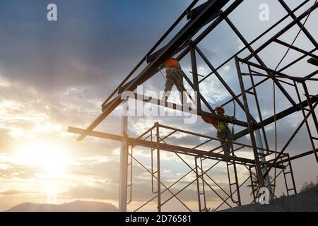 Silhouette d'ouvrier de construction sur la structure de toit dans le chantier de construction, concept équipement de hauteur de sécurité.