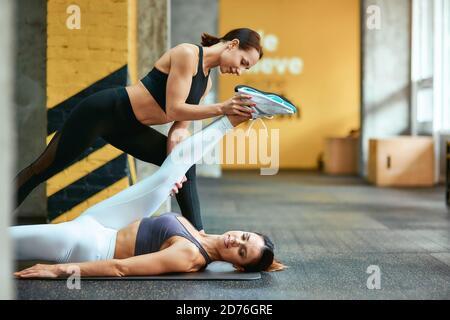 Corps flexible. Jeune belle femme caucasienne couchée sur le tapis de yoga à la salle de gym et faisant des exercices d'étirement avec l'aide de la femme entraîneur personnel à la salle de gym. Concept de sport et de mode de vie sain