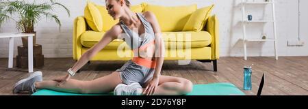 Photo panoramique de l'entraînement sportswoman sur un tapis de fitness près des sports bouteille à la maison Banque D'Images